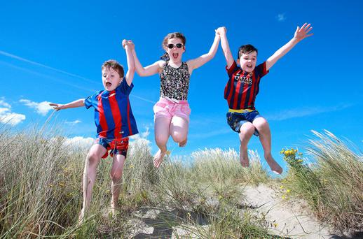 Ten year old Ella Troy jumps off the sandunes with Aidan [7] and Cian [6] Cullen from Santry, on Dublin's Dollymount Strand. Photo: Frank Mc Grath