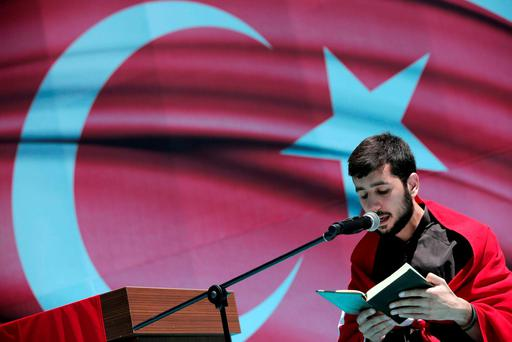 A teen reads from the Koran during a pro-government protest against the attempted coup in Istanbul. Picture Credit: AP Photo/Lefteris Pitarakis