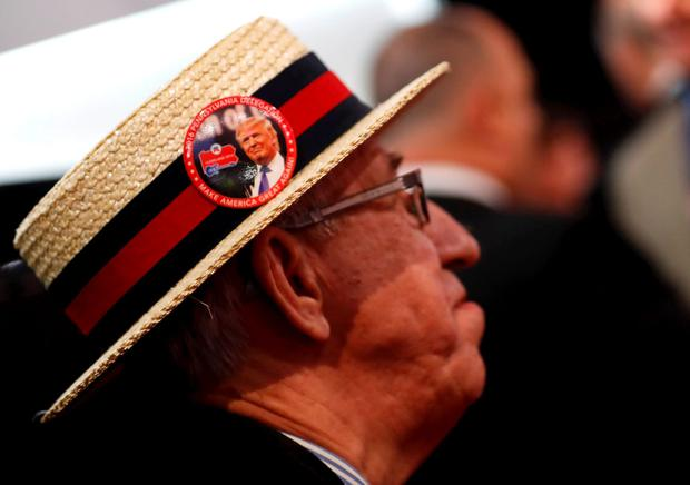 A supporter of Republican U.S. presidential candidate Donald Trump sports a button on his hat with Trump's image during the second day of the Republican National Convention in Cleveland, Ohio