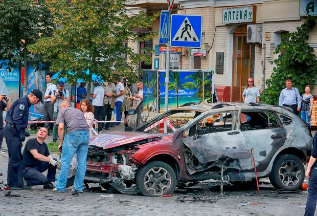 Forensic experts examine the wreckage of a burned car in Kiev, Ukraine (AP Photo/Efrem Lukatsky)