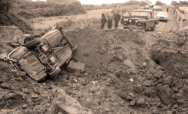 The twisted remains of the car lie upended beside a huge crater after the explosion that killed Christopher Ewart-Biggs and civil servant Judith Cooke
