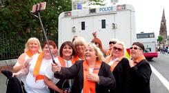 Orangewomen take a selfie beside a police vehicle at the July 12 parades in Belfast. Photo: Paul Faith/Getty
