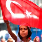 A Turkish girl wearing a headband bearing the name of Turkish president Recep Tayyip Erdogan waves her national flag during a pro-government demonstration in front of the old parliament building, in Ankara, Turkey. Photo: Hussein Malla/AP