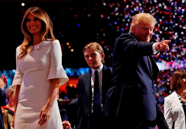 Balloons and confetti fall as Republican U.S. presidential nominee Donald Trump points into the crowd with his wife Melania (L) and his son Barron (C) at his side at the end of the final session of the Republican National Convention in Cleveland, Ohio, U.S. July 21, 2016. REUTERS/Mark Kauzlarich TPX IMAGES OF THE DAY
