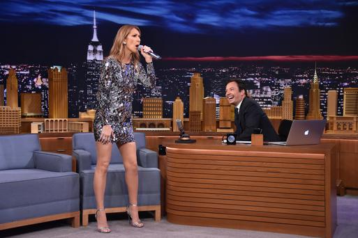 NEW YORK, NY - JULY 21: Host Jimmy Fallon (R) looks on as singer Celine Dion performs on