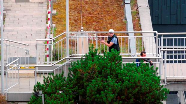 A screen grab taken from video footage shows plain clothes police officers attending the scene of a shooting rampage at the Olympia shopping mall in Munich, Germany July 22, 2016. dedinac/Marc Mueller/ handout via REUTERS NO ARCHIVES. FOR EDITORIAL USE ONLY. NOT FOR SALE FOR MARKETING OR ADVERTISING CAMPAIGNS. THIS IMAGE HAS BEEN SUPPLIED BY A THIRD PARTY. IT IS DISTRIBUTED, EXACTLY AS RECEIVED BY REUTERS, AS A SERVICE TO CLIENTS.