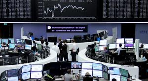 Traders work at their desks in front of the German share price index, DAX board, at the stock exchange in Frankfurt