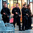 Police officers keep guard as shoppers are escorted from inside a Munich shopping centre. Sven Hoppe/dpa via AP