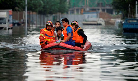 Rescuers use a raft to transport people along a flooded street in Shenyang in northeastern China's Liaoning Province