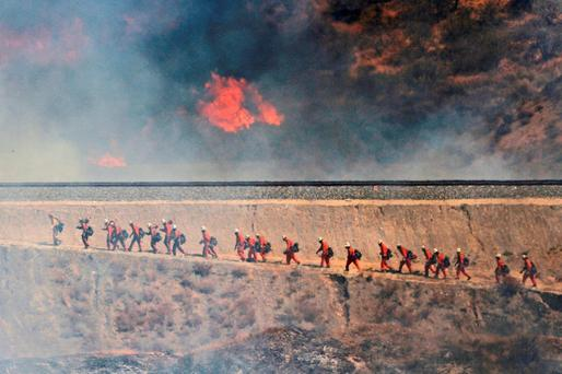 A fire crew approaches as a wildfire burns on Friday. (Katharine Lotze/The Santa Clarita Valley Signal via AP)