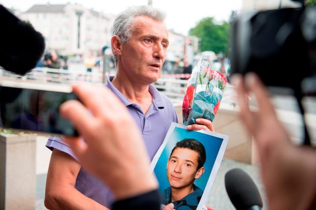Shock: The father of a victim shows a picture of his son near where the shooting took place. Photo: Sebatian Widmann/AP
