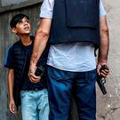 A Turkish police officer questions a young Kurdish boy in Diyarbakir. Photo: Getty