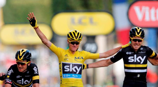 Yellow jersey leader and overall winner Team Sky rider Chris Froome of Britain celebrates with team mates on the finish line