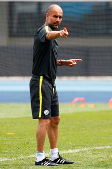 Pep Guardiola makes a point to his players during training yesterday. Photo: Reuters
