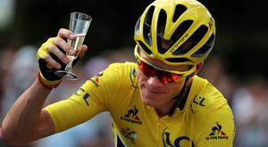 Chris Froome, wearing the overall leader's yellow jersey, celebrates with a glass of champagne on the Champs Élysées. Photo: AP