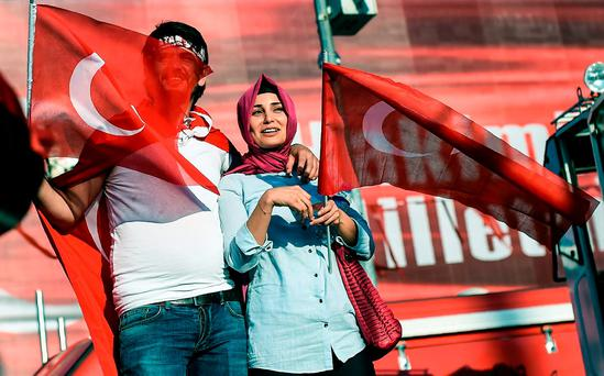 Demonstrators wave Turkish flags in Istanbul's Taksim Square yesterday during the first cross-party rally to condemn the coup attempt against President Recep Tayyip Erdogan. Photo: AFP/Getty