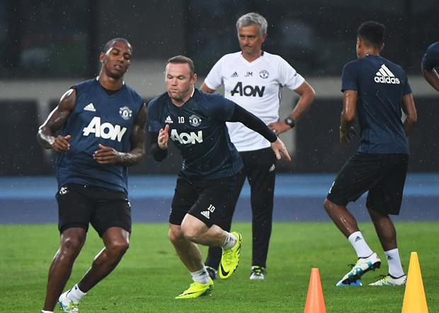 Manchester United's Wayne Rooney (C) sprints as coach Jose Mourinho (back) looks on during a training session a day before the 2016 International Champions Cup football match between Manchester City and Manchester United, in Beijing on July 24, 2016. / AFP / GREG BAKER (Photo credit should read GREG BAKER/AFP/Getty Images)