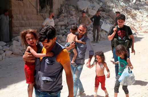 Syrian men carry injured children amid the rubble of destroyed buildings following reported air strikes on the rebel-held neighbourhood of Al-Mashhad in the northern city of Aleppo. Syrian leader Bashar al-Assad has repeatedly justified the attacks by describing the rebels as 'terrorists' Picture: AFP/Getty