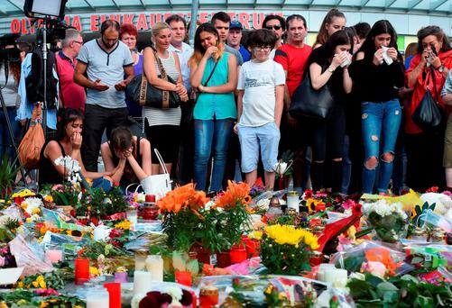 People mourn front of the Olympia Einkaufszentrum shopping centre in Munich Picture: AFP/Getty