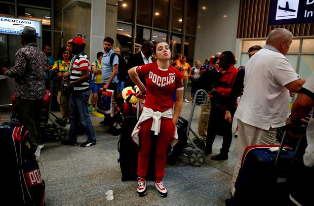 A member of Russia's Olympic team stands with her belongings during the team's arrival in the airport in Rio de Janeiro, Brazil, July 24, 2016. REUTERS/Pilar Olivares