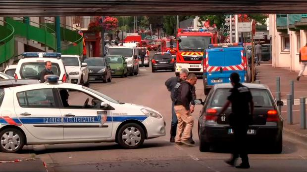 Police officers speak to a driver as they close off a road during a hostage situation in Normandy, France (BFM via AP)