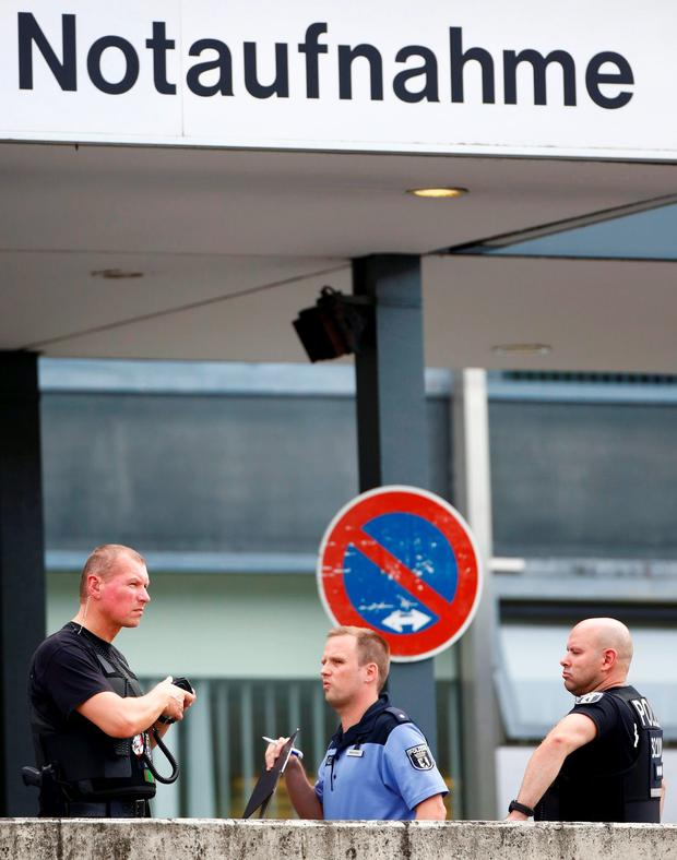 Police stand outside the university clinic in Steglitz, a southwestern district of Berlin, July 26, 2016 after a doctor had been shot at and the gunman had killed himself. REUTERS/Hannibal Hanschke
