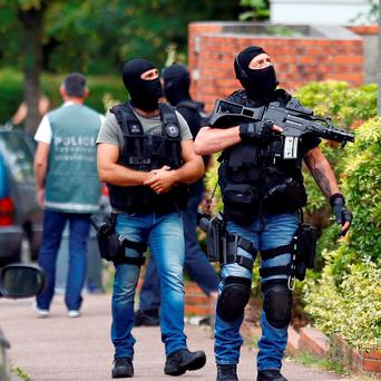 Hooded Police officers conduct a search in Saint-Etienne-du-Rouvray, Normandy, France, following an attack on a church that left a priest dead. (AP Photo/Francois Mori)
