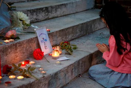 A young girls prays near flowers and candles at the town hall in Saint-Etienne-du-Rouvray. Photo: Reuters