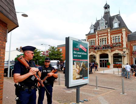 French police officers stand guard in front of the city hall at Saint-Etienne-du-Rouvray, near Rouen, after an attack on a church that left an 85-year-old priest dead. Photo: Francois Mori/AP