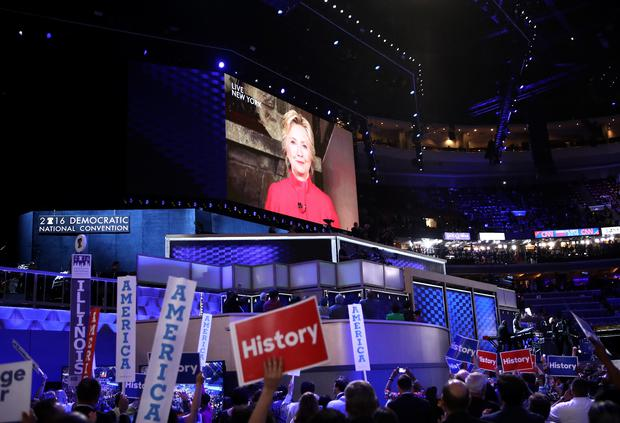 Delegates cheer as a screen displays Democratic presidential candidate Hillary Clinton delivering remarks to the crowd during the evening session on the second day of the Democratic National Convention at the Wells Fargo Center, July 26, 2016 in Philadelphia. (Photo by Jessica Kourkounis/Getty Images)