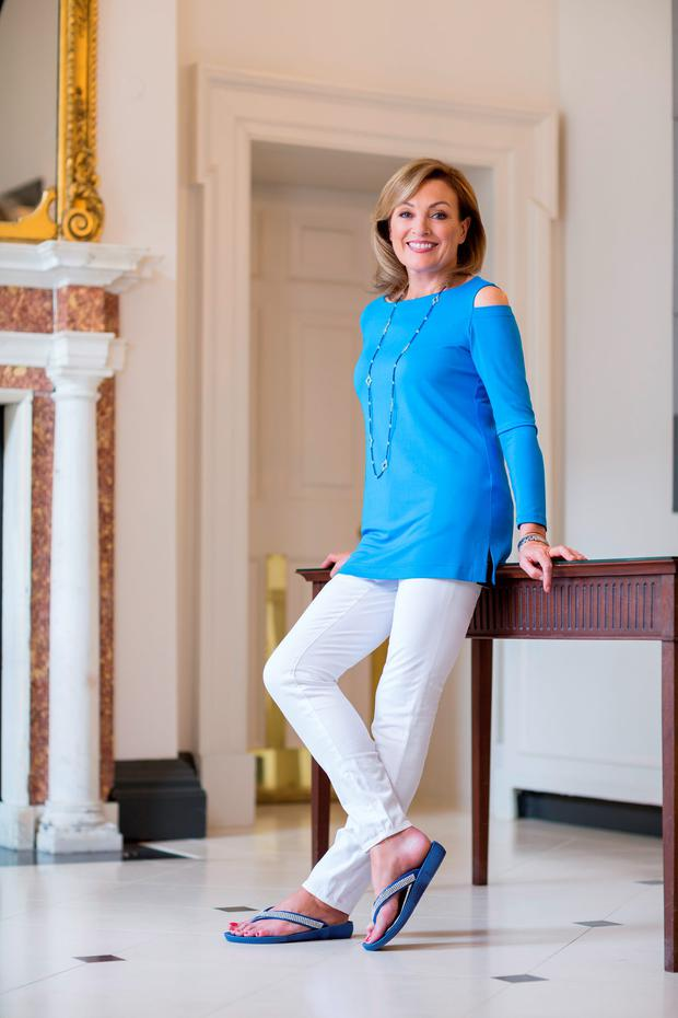 Mary Kennedy wears 'Gigi' top in azure blue, €595; AG white jeans, €235 and 'Darcy' aquamarine necklace, €395. All from Louise Kennedy, 56 Merrion Square, Dublin. Sandals, Mary's own. Photo: Patrick Bolger