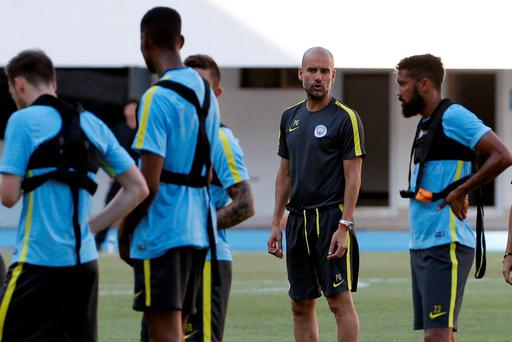 Pep Guardiola (2nd R) attends a training session