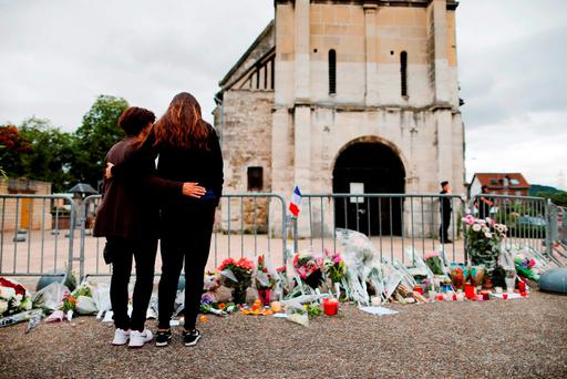 People stand at a memorial in front of the Saint-Etienne du Rouvray church, where Father Jacques Hamel was killed. Photo: Getty