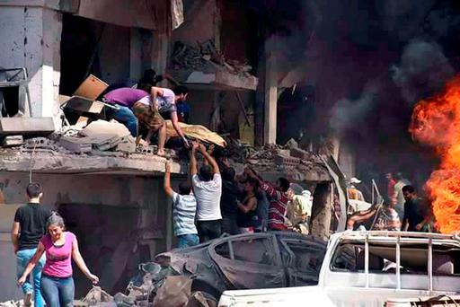 A photo released by the Syrian official news agency Sana, shows Syrians carrying the body of a victim from a building damaged when twin bombings struck the Kurdish town of Qamishli, where an Irish medic is based (SANA via AP)