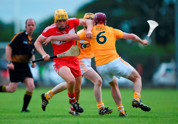 Derry's Mark McGuigan tries to get past Antrim's Paddy Burke. Photo: David Fitzgerald/Sportsfile