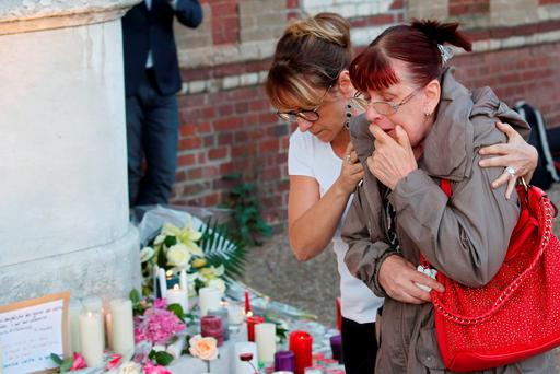Women pay tribute at the town hall in Saint-Etienne-du-Rouvray, near Rouen in Normandy, France, where Father Jacques Hamel was killed. Photo: Reuters/Pascal Rossignole