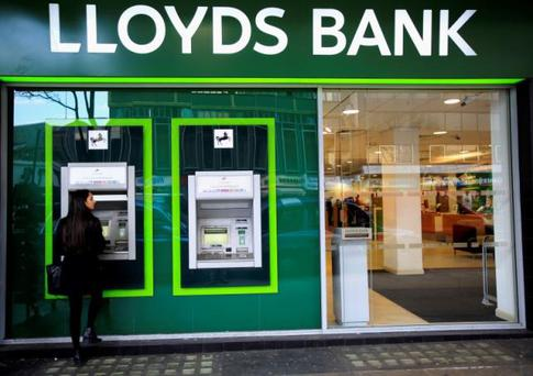A woman uses a cash machine at a Lloyds Bank branch in central London. REUTERS/Paul Hackett