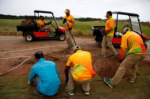 Workers lay turf on the Olympic golf course in Rio De Janeiro yesterday. Photo: Reuters