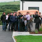 The coffin of jockey JT McNamara is carried by family and friends from his home in Limerick en route to the removal. Photo: Brian Gavin