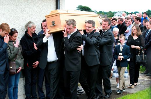 Friends and family carry the remains of jockey JT McNamara past a guard of honour by fellow jockeys,after funeral mass at St Michaels Church in Manister, near Co Limerick. Picture Credit : Frank Mc Grath