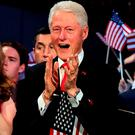 Former US President Bill Clinton applauds his wife. Photo: Robyn Beck/Getty Images