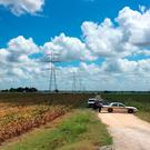 Police cars block access to the site where a hot air balloon crashed early Saturday, July 30, 2016, near Lockhart, Texas (AP Photo/James Vertuno)