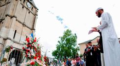 Muslims put flowers and hold a minute of silence in front of the church if Saint-Etienne-du-Rouvray, western France, where French priest Jacques Hamel was killed on July 26. Photo: AFP/Getty Images