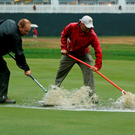 Workers use squeegees to push water from overnight heavy rain off the 18th fairway during the second round of the PGA Championship golf tournament at Baltusrol Golf Club. (AP Photo/Mike Groll)