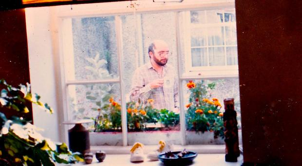 Charles Self seen through the kitchen window of Annesley Mews having a cup of tea in the courtyard