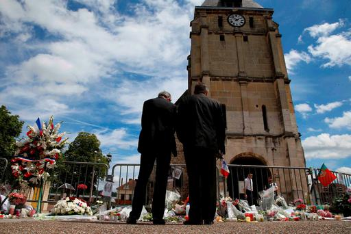 Men stand near flowers left in tribute to French priest Father Jacques Hamel outside the parish church at Saint-Etienne-du-Rouvray, near Rouen, France. Photo: Pascal Rossignol/Reuters
