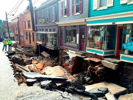 Workers gather by street damage after Saturday night's flooding in Ellicott City (Kevin Rector/The Baltimore Sun via AP)