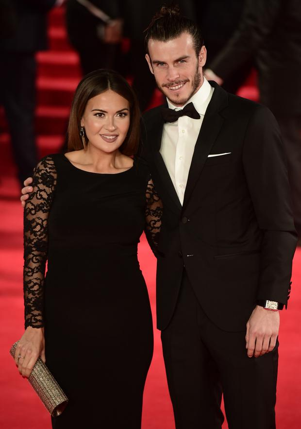 Welsh footballer Gareth Bale (R) and his partner Emma Rhys Jones pose on arrival for the world premiere of the new James Bond film 'Spectre' at the Royal Albert Hall in London on October 26, 2015.AFP PHOTO / LEON NEAL