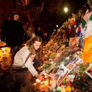 A woman lights a candle as a Tricolour hangs at a memorial outside the Bataclan in Paris. Photo: Mark Condren