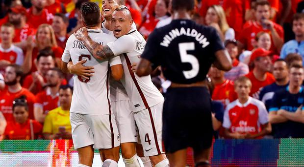 Roma forward Edin Dzeko, second from left, is congratulated by teammates Kevin Strootman, left, and Radja Nainggolan, third from left, after scoring a goal against Liverpool